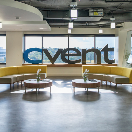 Image shows the Cvent offices with a large logo against a window with blue sky behind.