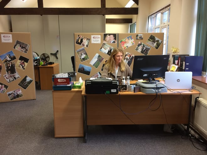 Lucy sits at a computer responding to email. Wedding pictures are posted around her cubicle.