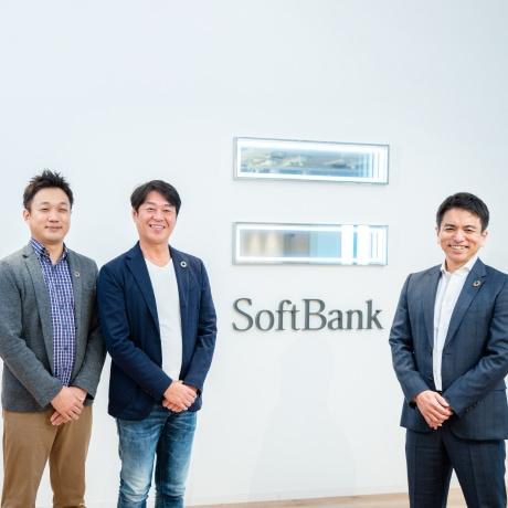 Image of Kunihiro Fujinaga, Keiichi Makizono and Kazushi Iizuka standing in front of Softbank's logo