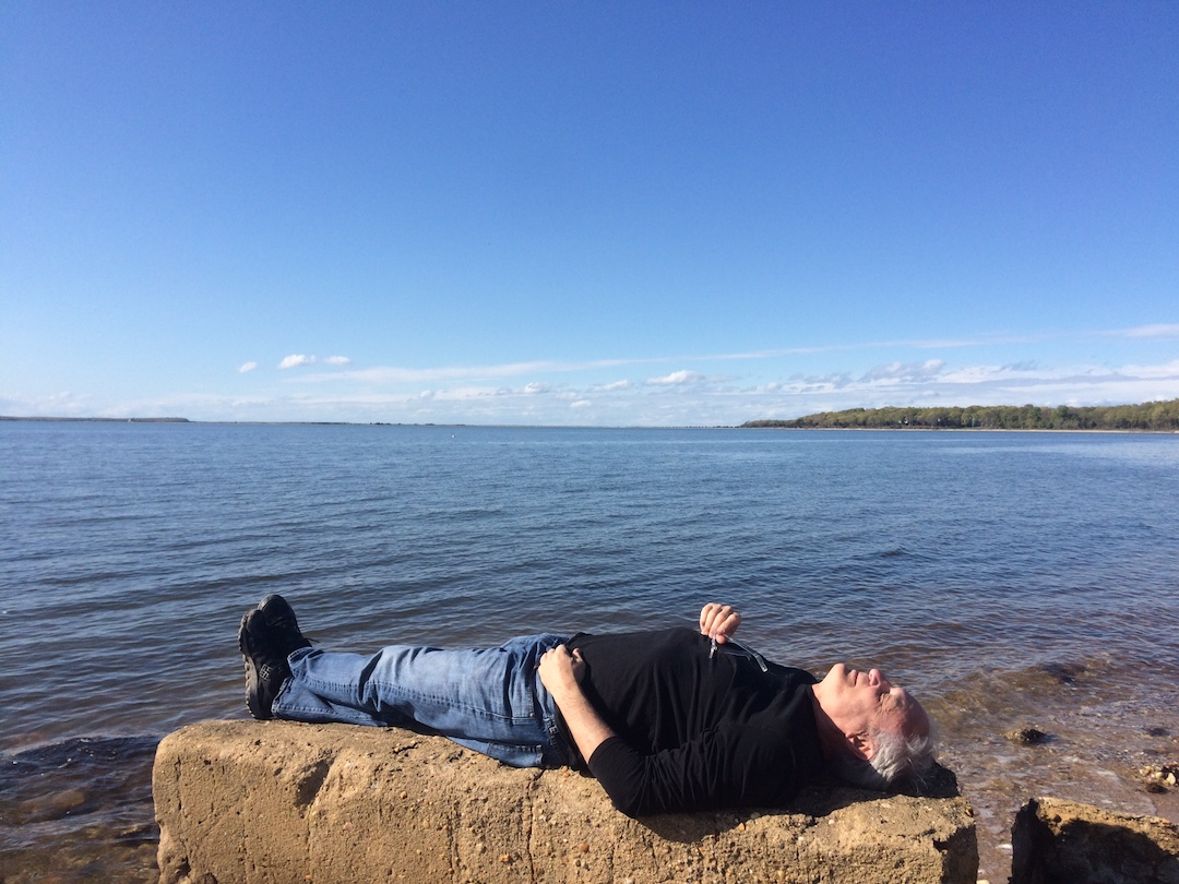 Paul is on his back relaxing on a clear and isolated beach.