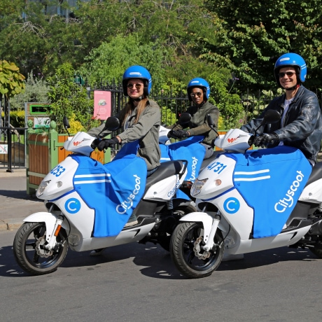 An image of three people riding Cityscoot electric motor scooters.