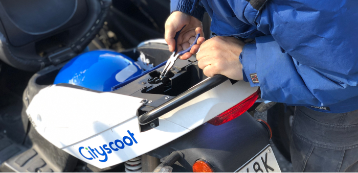 A person using pliers to fix a Cityscoot scooter