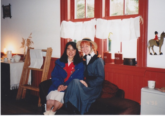 Erin wears a orange yarn wig and hat and poses with a coworker in a room with red trim and a Canadian Mountie decoration.