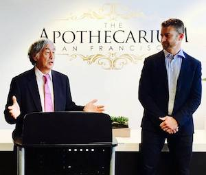 Two men in suits stand in front of an ornate logo for The Apothecarium.