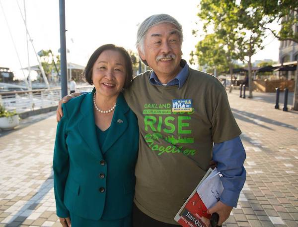 Dr. Huen is wearing a shirt supporting Mayor Jean Quan that reads Oakland Rise Together and posing with his wife, Jean Quan.