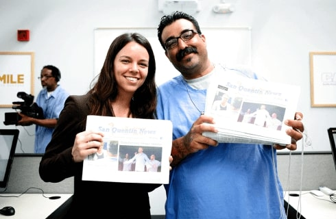 Slack volunteer Kathryn Hymes and a person in an incarcerated setting stand smiling alongside each other while both holding up a copy of the San Quentin News.