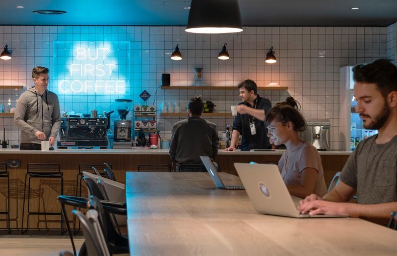 """Slack-Mitarbeiter, die gemeinsam arbeiten und in einer offenen Küche miteinander lachen. Auf dem Schild im Hintergrund steht """"But first, coffee"""" (Aber zuerst einen Kaffee)."""